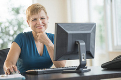 Image of Lady Smiling from desk.