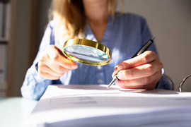 Image of Woman using magnifying glass to investigate.